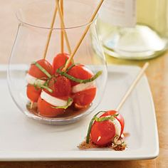Mini Caprese Bites - Serve these mini tomato and mozzarella skewers in individual glasses as an appetizer at a seated dinner party, or arrange on a platter for your buffet. www.MyRecipes.com
