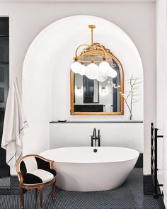 """Chandeliers and statement pendants aren't limited to the living and dining rooms of a house. """"A chandelier adds ambience to the bath-time…"""