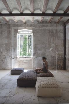 Large pouffs, textured cement floor, half moon ceiling, roughed walls. Love it all