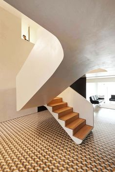 The U-shaped staircase with thick white balustrades and wooden treads leads from…