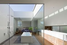 The Art of the Japanese Bath | House in Machikaneyama  by Kita Chikara.  This bath and shower is located in a terrace. The double-layered glass skylight can be open, making it feel like an outdoor extension of the en suite bathroom.