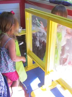 "Painting with shaving cream on a DIY ""window"" sensory board."