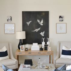 Chic living room features a 4 drawer console table under a black and white canvas art piece flanked by ivory nailhead wingback chairs lined with white and navy stripe pillows.