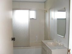 Bathroom of 2 bedroom 1980's home @ Awatapu Drive, Whakatane. With original soft apricot colour, frosted glass shower-bath divider/ door, cute geometric shaped mirror, apricot plastic taps and sink unit. (in Oct 2014)