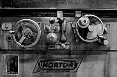 .Black and white image of Antique industrial machinery control wheels and knobs in a metal machine shop..