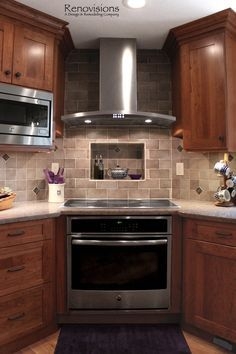 Kitchen remodel by Renovisions. Induction cooktop, stainless steel appliances, cherry cabinets, shaker cabinets, under cabinet lights, tuscan-clay-look porcelain tile backsplash, quartz countertop, hardwood flooring, corner stove.