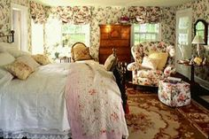 A fantasy of floral bouquets with chintz fabric lining the walls, draping the windows, and slipcovering the various upholstered pieces throughout. There is an eclectic mix of furniture styles, with a Georgian chest on chest, carved French side chair, Queen Anne side table, and English-style brass bed.