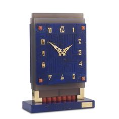 BOUCHERON. An Art Deco lapis lazuli and coral desk clock. Of geometric design, the rectangular-shaped lapis lazuli clock face carved with a linear design, applied with yellow gold Arabic numerals and open work hands, with mechanical movement, mounted on a stepped agate surround, supported by a lapis and yellow gold base embellished with coral sections, circa 1929, the base and winding stem signed Boucheron Paris. £ 150,000