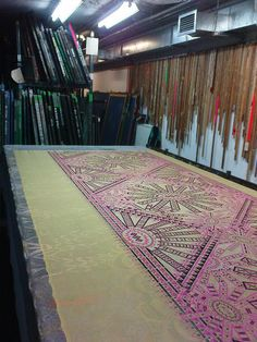 Zandra Rhodes studio basement, London, where short runs of fabrics are screen printed to then be made up into samples for the next collection. This print in pink and black is called 'Star Dust.' [Photo and more from knitpurlandstitch.wordpress.com]