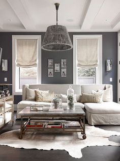 ♅ Dove Gray Home Decor ♅ casual gray living room. Roman shades over baseboard heat, gray walls, white trim, white hide rug, dark wood floors, gray furniture