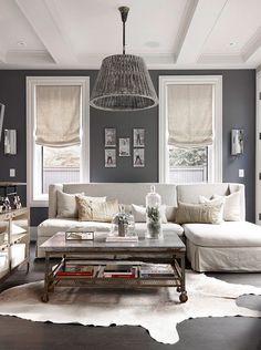 ♅ Dove Gray Home Decor ♅ casual gray living room. Roman shades over baseboard heat, gray walls, white trim, white hide rug, dark wood floors, gray furniture