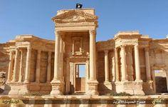 (Maio) Imagem divulgada pela mídia jihadista mostra uma bandeira do Estado Islâmico no topo do teatro romano da cidade de Palmira