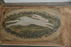 Running Rabbit hand painted on a kitchen cabinet door with blueberries surrounding it.