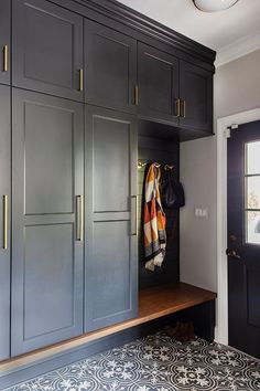 A black door with glass panels opens to chic black and white quatrefoil floor tiles complementing black closed lockers donning brass pulls and fitted framing a black shiplap backsplash holding brass hooks over a stained wood bench.