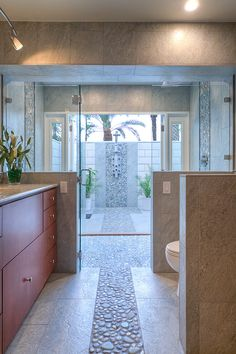 This breathtaking bathroom features a large, open-air shower. French doors beyond the shower open into a private courtyard with an outdoor shower, with the two spaces linked by a common design theme based on river rock detail. Indoor Outdoor Bathroom, Outdoor Sinks, Outdoor Showers, Beautiful Bathrooms, Modern Bathroom, Master Bathroom, Minimalist Bathroom, Bath Tiles, Bathroom Tile Designs