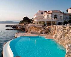 """Cliffside Pool, Hotel du Cap Eden-Roc (France). """"The majestic infinity-edge pool...filled with ocean salt water and heated on cooler days, it looks out on the Lérins Islands and the glassy Cannes Bay, where the gin palace yachts of the celebrities and tycoons who stay here bob on the water. On a secluded cement terrace, hidden among rocks above the pool, cocktail waiters tend to guests reclining in private cabanas on deck chairs under glossy white umbrellas."""""""