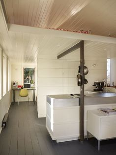 Garage kitchen after remodel. A utilitarian core contains the kitchen, bathroom, closet, and loft ladder. The kitchen's walls are clad with recycled wooden boards trimmed with horizontal battens that hide the oven and refrigerator from view