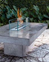 "This could make a fabulous bar for adjacent a barbecue area. Sleek outdoor firepit adds a warm glow and wonderful ambient light. Table and base handcrafted of low-lustre polished concrete; imported.  Glass guard made in the USA of heat-strengthened glass.  Uses bio-fuel (not included).  62""W x 40.5""D x 32""Tall."