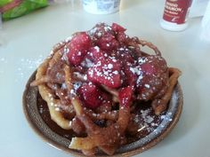 Fried dough topped with fresh strawberries and powder sugar