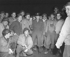 General Dwight Eisenhower poses with a group of soldiers during a visit to the Battle of the Bulge battlefield. The soldiers were members of the 334th Anti-Aircraft Artillery (AAA) Battalion