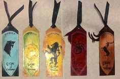 About: Custom made bookmarks with a Game of thrones Theme (Back View)  Medium: polish, colored pencil, ribbon, marker etc Size: unknown Date: June 26, 2014 Paper: Unknown #customMade #handmade #bookmarks #color #gameOfThrones #GoT #houses #art #drawings #prisma #colors #polish #lamonated #painting #lion #wolf #elk #dragon #gold #flower #creativityHasNoLimits