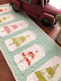Mix and match your favorite red and green prints in this adorable take on a classic Christmas tree motif. The ever-popular mason jar makes an appearance to make this table runner one of a kind! Finished size: x Design by Margot Lan. Purple Christmas Tree, Christmas Tree Quilt, Christmas Quilt Patterns, Christmas Jars, Christmas Crafts, Christmas Quilting, Christmas Tables, Coastal Christmas, Quilted Table Runners Christmas