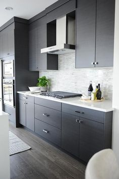 Modern gray kitchen features dark gray flat front cabinets paired with white quartz countertops and a gray mosaic tiled backsplash.