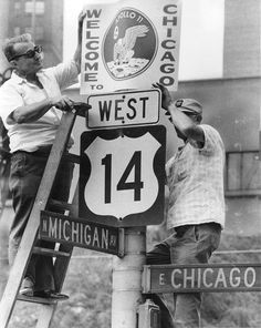 """Sign hangers (left) Nick Padula and James Stewart, both city workers, put up """"Welcome Apollo 11"""" signs along Michigan Avenue. The signs were posted along the parade route for Apollo 11 astronauts and their families."""