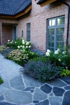Perfect match of colors: roof, windows, hardscaping match, brick and flowers work beautifully contrasting the slate gray.