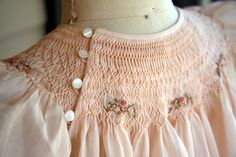 """Pale peach batiste shoulder button bishop with """"Roses All Around"""" smocking design. Made by Trudy Horne."""