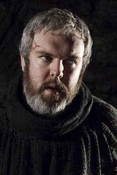"""Hodor is a dim-witted stableboy at Winterfell.  His real name is Walder Frey. He can only say one word - """"Hodor."""" He is over 7 ft. tall and it's been suggested that he is at least part-giant. When Bran became crippled, a basket was designed for Hodor to carry him around. Hodor hid in the crypts with the Stark boys, Osha and the Reeds during the Sack of Winterfell.  He is currently in the cave of the three-eyed crow with Bran and the Reeds, and Bran often wargs into him."""