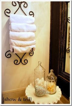 Plate rack holder repurposed to hold towels on and a cake stand for q tips and cotton balls