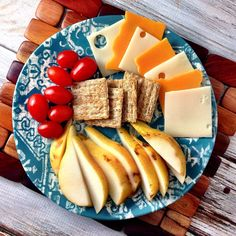 Grape tomatoes, wheat crackers, cheese, and pears.