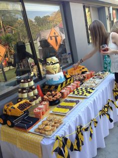 Under Construction Food Table. Cake by Design a Cupcake Party - Brisbane, Australia. DIY Black Cake Stands made using Black Plates on top of upside down Black bowls from IKEA. Caution Tape and Hazard tape from BUNNINGS used to make bunting and decorate Cake riser. Popcorn boxes made using a free printable template and decorated using a road sign printable made by me. Choc-orange Macarons, jelly slice, LCM bars, sugar cookies, cupcakes and quiches all made by me.