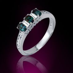 Set in 18K gold, this ring features three oval shape natural alexandrites set in prongs and accompanied by two emerald cut white diamonds and a diamond dressed shank.