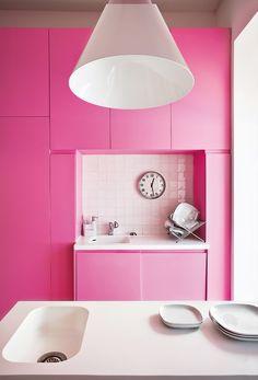 Casa cápsula en Lisboa. El arquitecto Pedro Gadanho diseñó la cocina en madera y corian blanco, y la dueña eligió el color rosa chicle.