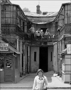 """În Piaţa Sf. Vineri, chiar unde întorcea tramvaiul 19, era una dintre curţile """"potcoavă"""" ale clădirii din Calea Văcăreşti nr. 8-12. Ansamblul de secol XIX, cu planul într-o formă unică de E, avea două astfel de buzunare, iar în imagine este cel dintre nr. 10 (la dreapta) şi 12 (la stânga). La stradă erau două barăci: în stânga, un birou de copiat acte, iar la dreapta, o ceasornicărie. La parterul corpurilor erau, de asemenea, spaţii comerciale şi ateliere. Spre exemplu, la nr. 12 funcţionau… Old Pictures, Old Photos, Bucharest Romania, Old City, Time Travel, Places To Visit, Louvre, Urban, Building"""