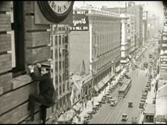 """Harold Lloyd's iconic scene in the silent film """"Safety Last"""" (1923).  One of the most famous images from the silent film era with Lloyd  clutching the hands of a large clock from the outside of a skyscraper."""