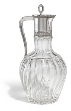 A FABERGÉ SILVER-MOUNTED CUT GLASS DECANTER, MOSCOW, 1908-1917 of baluster form, swirl fluted body, the collar mount with a band of chased palmettes, the hinged cover with ribbon-tied laurel wreath finial, struck K. Fabergé in Cyrillic beneath the Imperial Warrant, 88 standard, scratched inventory number 21803.