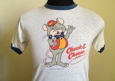 Vintage 1980s white and navy blue Chuck E. Cheese ringer t-shirt, listed from 1981. Print is black and red, while image is multicolored. Size: Large Brand: Screen Stars 50% cotton, 50% polyester The shirt is very soft and in very good vintage condition, with no visible stains or tears. Approximate measurements with garment laying flat (INCHES): Length (from top of shoulder at collar seam to bottom) : 25.5 Sleeve (from top of shoulder seam to cuff edge) : 7.5 Between Shoulder Sea...