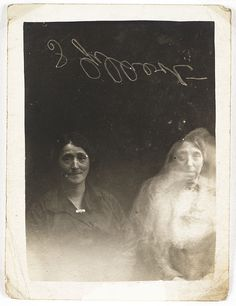 Two women with a spirit    The face of a young woman appears over the woman on the right of the photograph. The reverse of the photograph reads: 'Why is the child always pushing to the front?' and 'Do we get messages from the higher spirits?'; perhaps questions the women wanted answering. One of the sitters, at Hope's request, has signed the plate for authentication.    Collection of National Media Museum