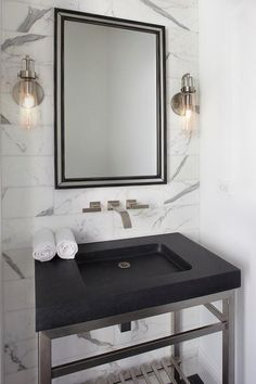 Modern black and gray powder room features a steel and black granite washstand paired with a polished nickel faucet mounted to marble wall tiles beneath a black beveled vanity mirror flanked by filament sconces.