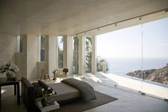Bedroom with a glass wall and view of the Pacific Ocean. - Daring Cliffside House Design In La Jolla, California