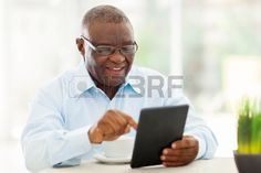 cheerful senior african american man using tablet computer at home Stock Photo