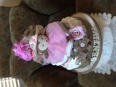Baby shower diaper cake. Lots of pink and burlap.  Monkey has baby shoes and socks on, along with a real tutu for future baby photos.   The center features Burt's Bee's products. On the back are several pairs of socks.  Baby head bands, a binky, binky leash and lots of diapers are all the extra's for this new arrival!