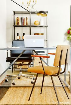 Office with white walls, silver bookshelf, silver desk, black leather chair, wood chair, brown rug, and black light fixture