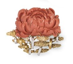 A carved coral, diamond and 18k gold flower brooch