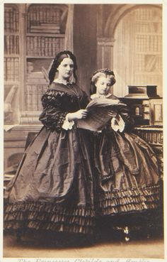 1861 photograph Princess Clotilde (left) and Princess Amalie standing side by side. Together they hold what looks like some sheet music. Backdrop of an interior with bookshelves.