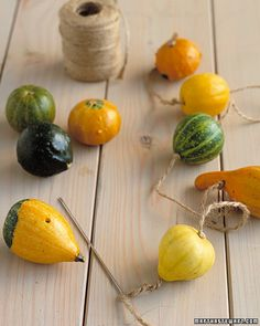 DIY Gourd Garland.  drill hole through, then use twine on a needle to thread gourds on, knotting before and after each.  hang inside or out.