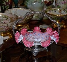Brides Basket/Centerpiece: Lovely Pink Cased Glass Brides Bowl with Clear Ribbon Ruffled Trim and Raised Enamel and Gild Blue and Yellow Floral Decor Sitting in Pairpoint #4719 SP Basket Featuring Grape/Ivy Decor